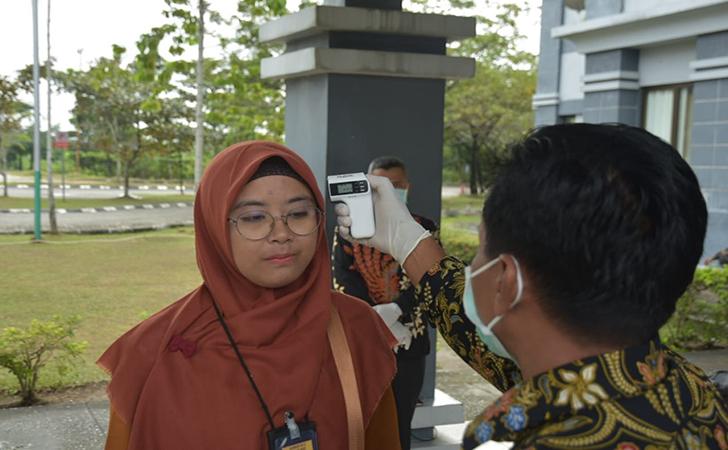 Pemeriksaan suhu tubun di depan pintu masuk gedung rektorat UIN Suska Riau